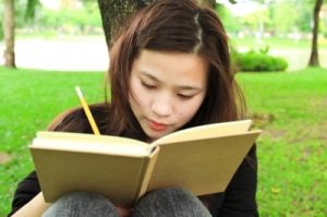 Young woman outdoors writing in a book