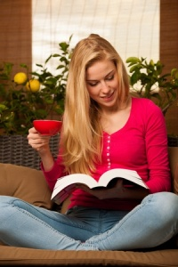 woman reading a book holding a cup of coffee