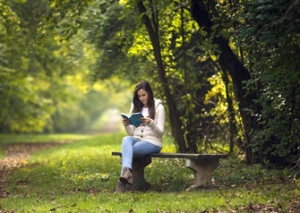 woman reading a book on a park bench