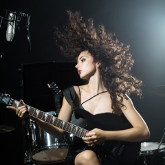 woman playing and electric guitar